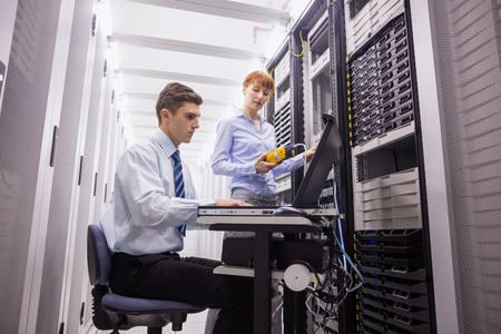man using computer: Team of technicians using digital cable analyser on servers in large data center