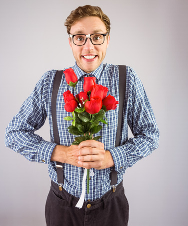eager: Geeky hipster holding a bunch of roses on grey background