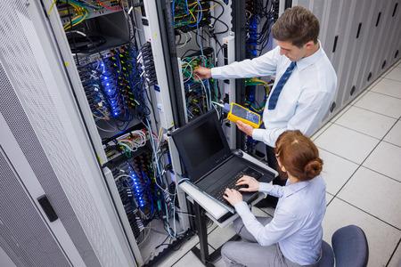 Cable network: El equipo de t�cnicos que utilizan analizador de cable digital en los servidores de centro de datos grande Foto de archivo