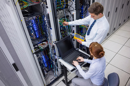 data center: Team of technicians using digital cable analyser on servers in large data center