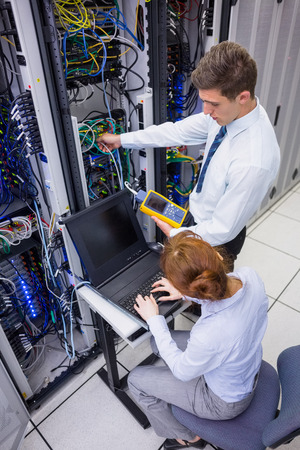 team power: Team of technicians using digital cable analyser on servers in large data center