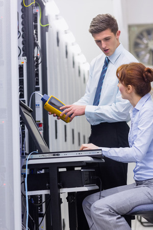 Team of technicians using digital cable analyser on servers in large data center photo