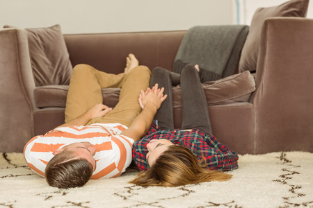 Cute couple lying on floor at home in the living room photo