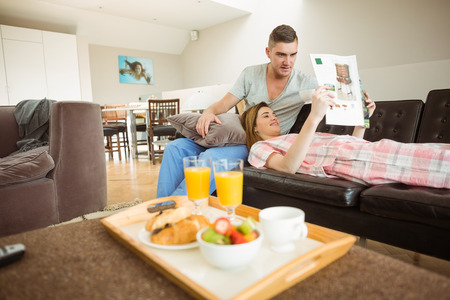 Cute couple relaxing on couch at breakfast at home in the living room photo