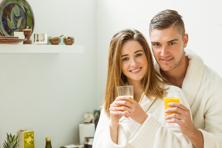 Couple drinking orange juice in bathrobes at home in the kitchen photo