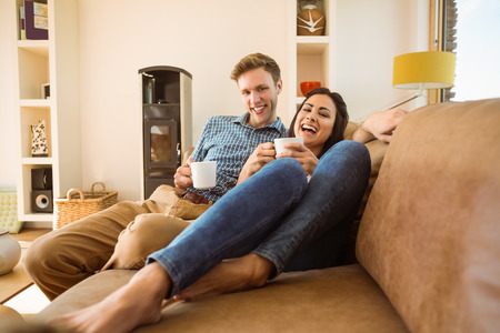 Happy young couple relaxing on the couch at home in the living room photo