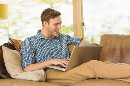 Young man relaxing on his couch with laptop at home in the living room photo