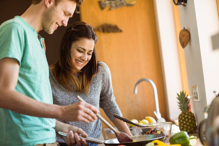adult couple: Cute couple preparing food together at home in the kitchen Stock Photo