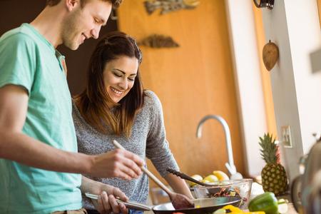 pareja en casa: Linda pareja de preparar la comida juntos en casa en la cocina