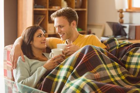Jong koppel knuffelen op de bank onder deken thuis in de woonkamer