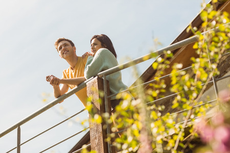 young adult men: Young couple standing and looking out outside on the balcony Stock Photo