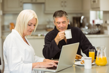 Mature couple having breakfast together woman using laptop at home in the kitchen photo