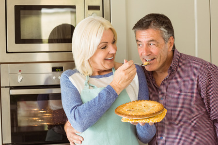 Happy mature blonde feeding pie to husband at home in the kitchen photo