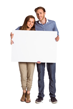 Full length portrait of couple with blank board over white background photo