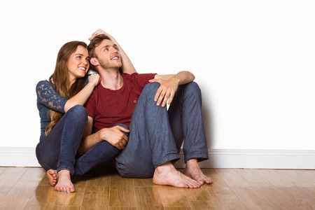 woman sitting on floor: Full length portrait of young couple sitting on floor