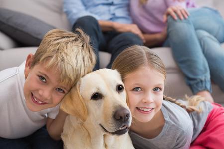 両親のリビング ルームで自宅のラブラドールと敷物の上の子供を見て 写真素材