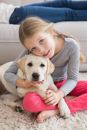 Happy little girl with her puppy at home in the living room photo