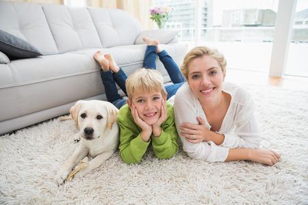 幸せな母と息子のリビング ルームで自宅で子犬と
