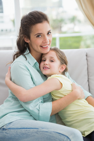 Cute mother and daughter on the couch at home in the living room photo