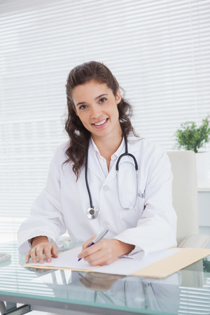Smiling vet sitting and writing notes in medical office photo