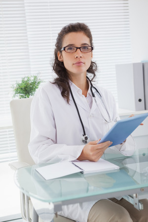 Vet sitting and holding tablet in medical office photo