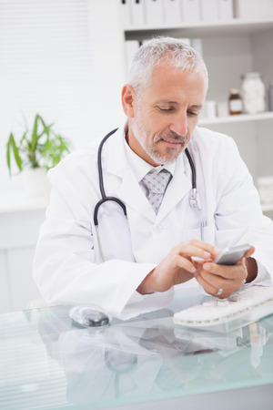Smiling doctor touching his phone in medical office photo