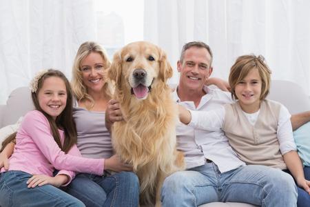 Familia linda que se relaja junto en el sofá con su perro en su casa en la sala de estar