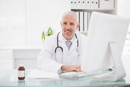 Happy doctor typing on keyboard in medical office