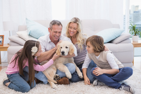 Smiling family with their pet yellow labrador on the rug at home in the living room