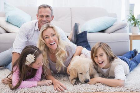 Laughting familie met hun huisdier gele labrador op het tapijt thuis in de woonkamer Stockfoto