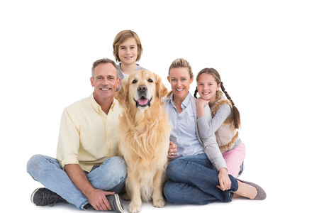 Portrait of smiling family sitting together with their dog on white background photo