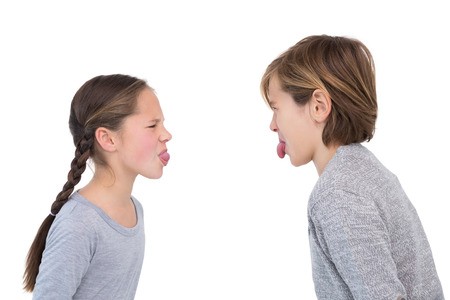 sacar la lengua: los hermanos y hermanas que se pegan la lengua en una pelea en el fondo blanco Foto de archivo