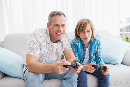 Son and father playing video games together on the couch at home in the living room photo