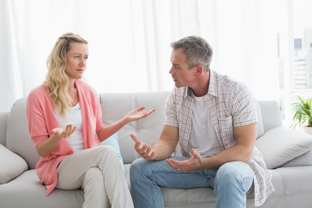 Unhappy couple having an argument on the couch at home in the living room Stock Photo
