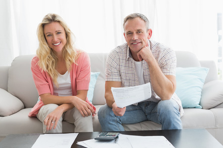 Couple doing their accounts sat in a couch at home in the living room photo