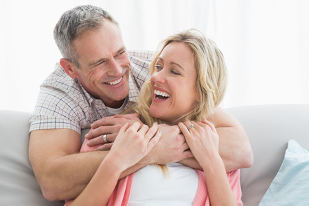 couple home: Content man hugging his wife on the couch at home in the living room Stock Photo