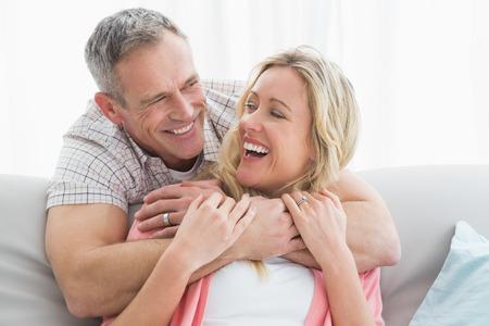 parejas: Hombre contenido abrazando a su esposa en el sof� en casa en la sala de estar Foto de archivo