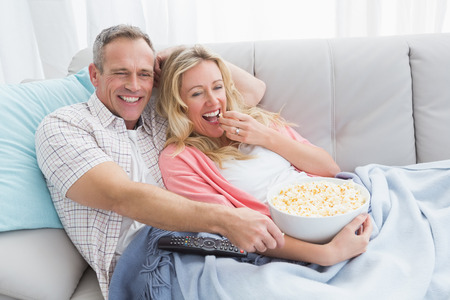 bowl of popcorn: Couple eating popcorn while watching television at home in the living room
