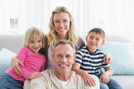 Portrait of a cheerful family on the couche at home in the living room photo
