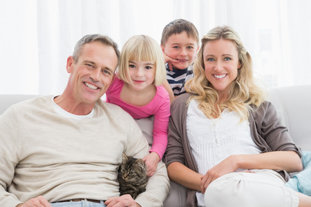 Happy family sitting with pet kitten together at home in the living room photo