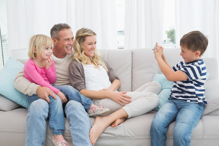 Son taking a photo of his family at home in the living room Stock Photo