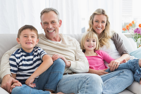 Portrait of a smiling family sitting on sofa at home in the living room photo