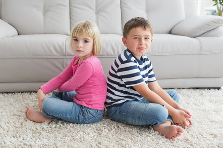 Unhappy siblings not speaking to each other at home in the living room photo