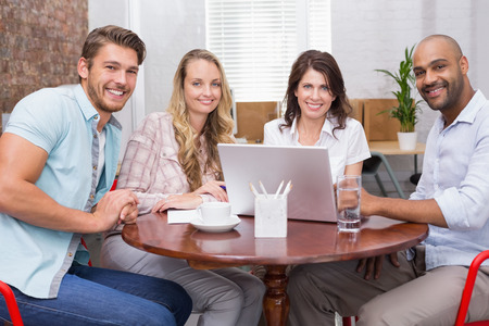 Smiling business team working together with laptop in the office photo