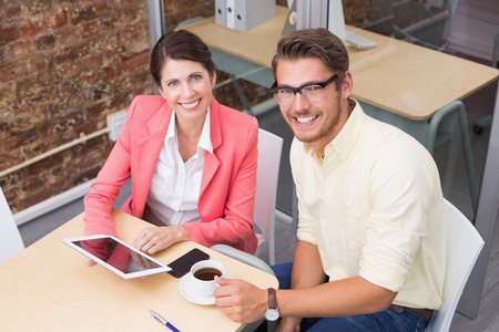 Business colleagues holding coffee cup and digital tablet in the office photo