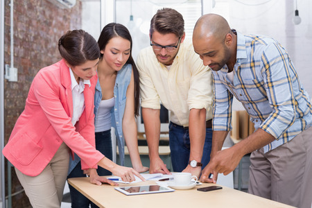 Businesswoman pointing something on tablet to his colleagues in the office photo