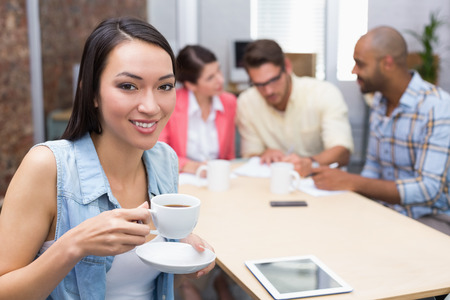 Woman drinking a coffee while his colleague work behind her in the office photo