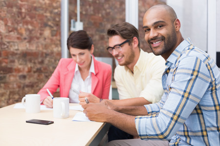 Smiling businessman looking at camera in meeting in the office photo