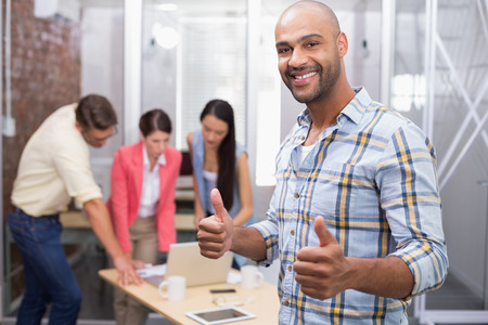 Happy businessman smiling at camera giving thumbs up in the office photo