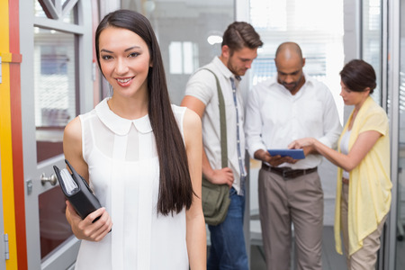 Smiling woman holding agenda in front of her colleague in the office photo